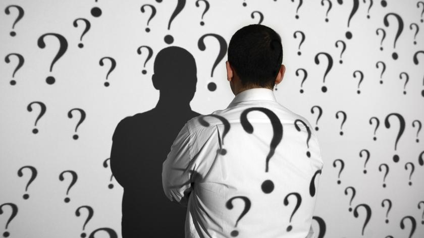 man stands in front of question marks