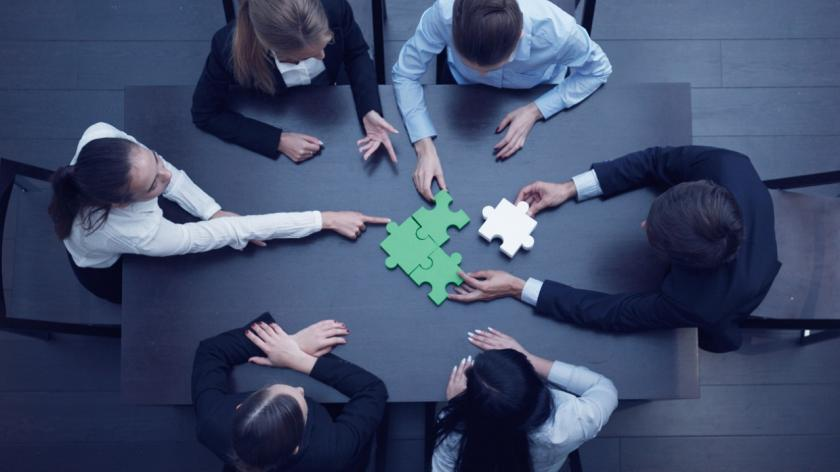 people in a meeting putting green and white puzzle pieces together