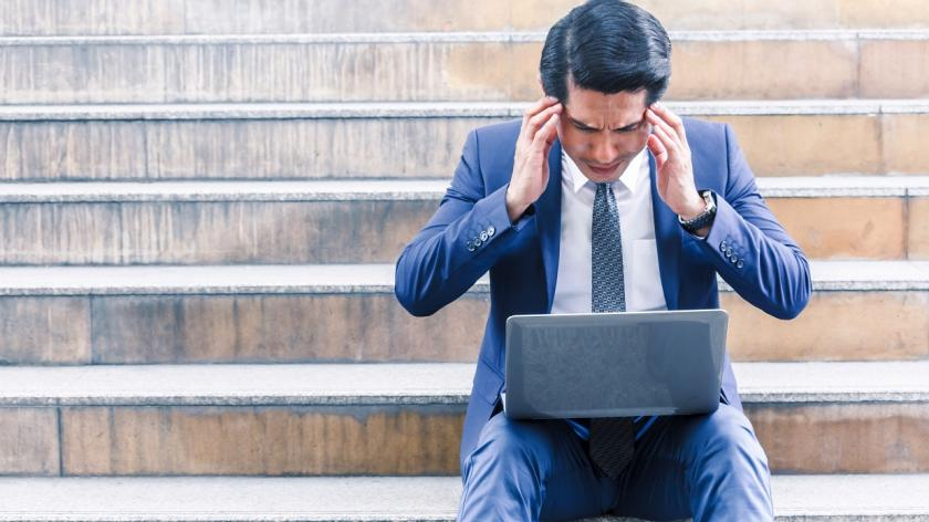stressed business man on steps looking at laptop