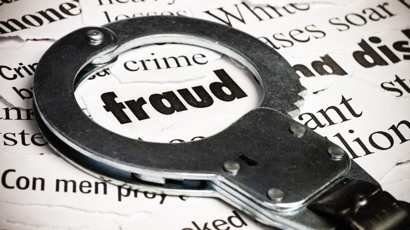 Handcuffs over newspaper with word fraud