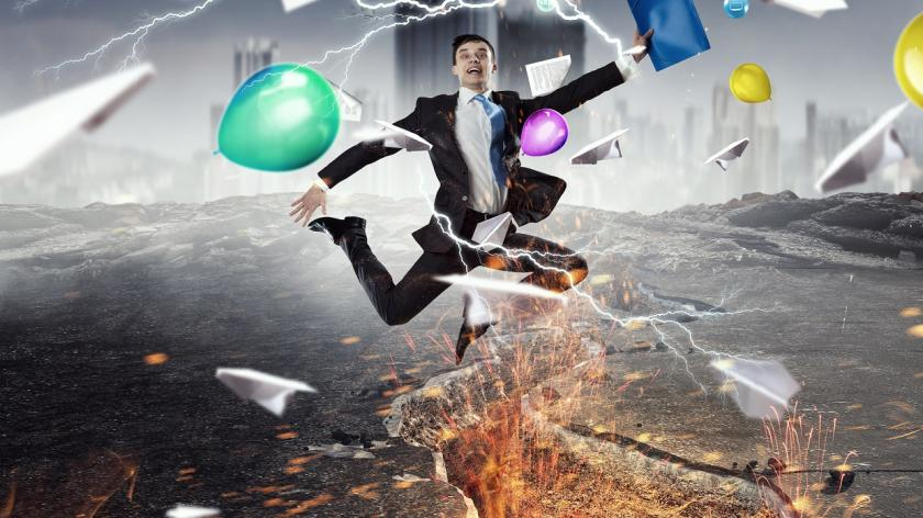 Man leaping over crack in the earth with folder