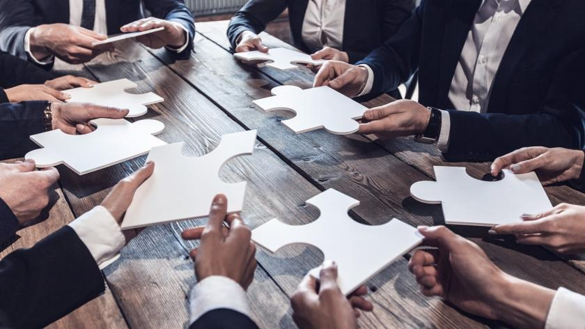 people around a table holding puzzle pieces