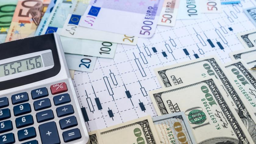 dollars and euros on a desk with calculator and graphs