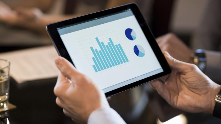 man holding a tablet with growth charts