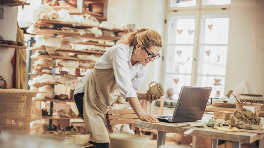 woman in pottery shop on her laptop