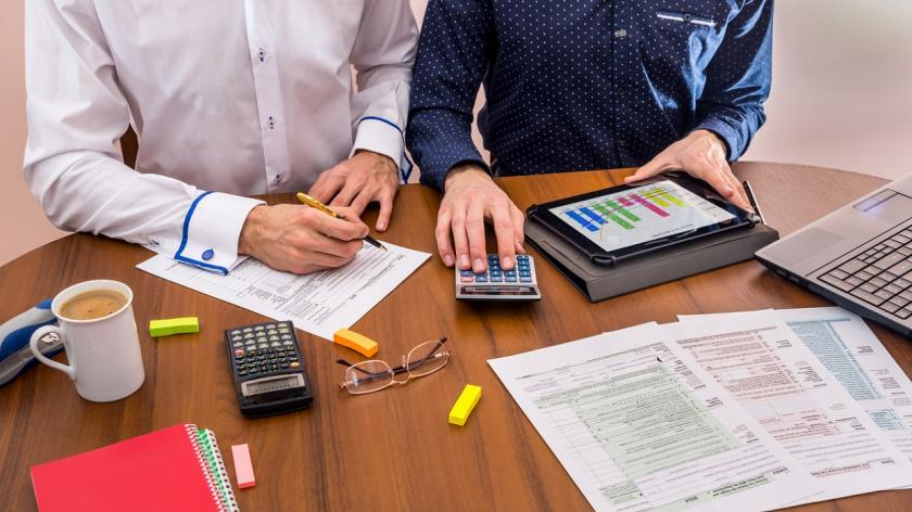 people work on tax forms with caluculator and  computer