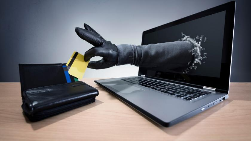 gloved hand coming out of a laptop taking a credit card