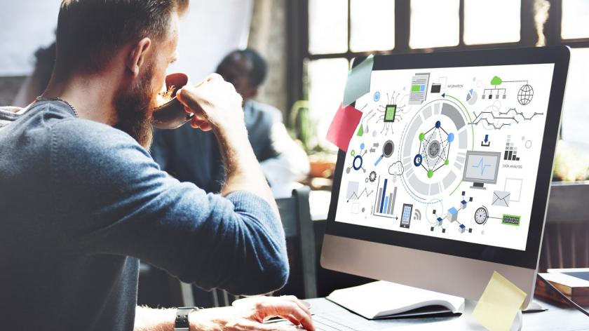 man looking at desk monitor with electronic images