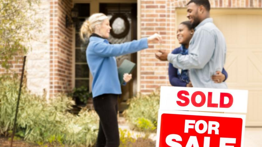 real estate agent hands keys to newly sold home