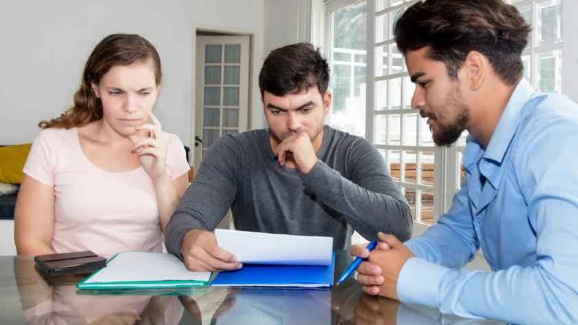 couple looking questionably at paperwork