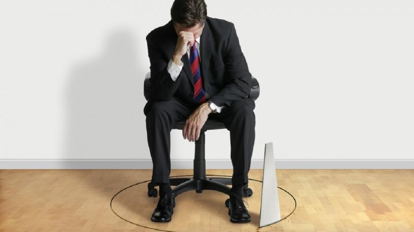 business man in chair with saw through the floor
