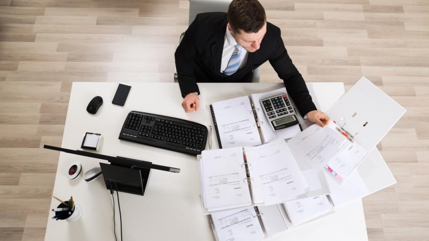 businessman looking over papers on a desk