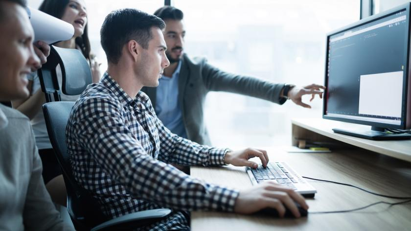 people in a meeting looking at computer monitor