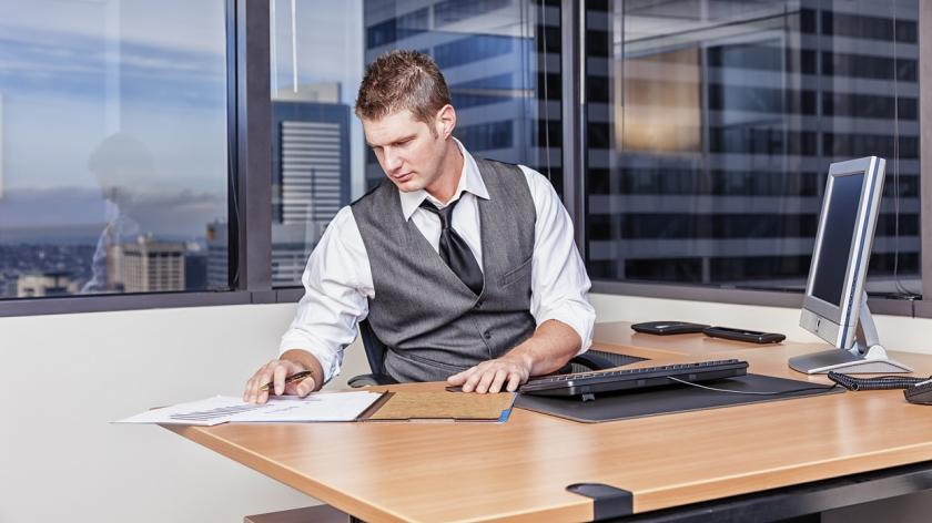 man shuffling papers on his desk