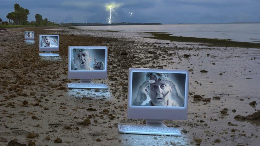 man in multiple computer screens on a stormy beach