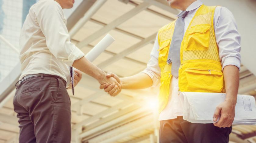businessman shakes hands with engineer