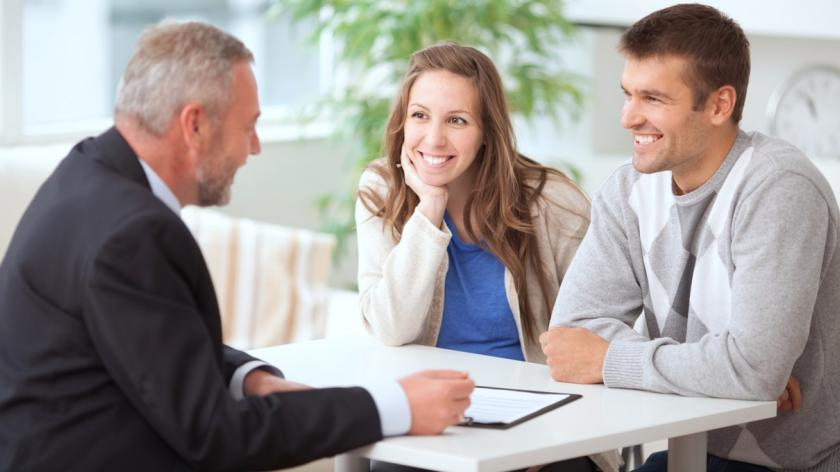 couple speaking to business man at desk