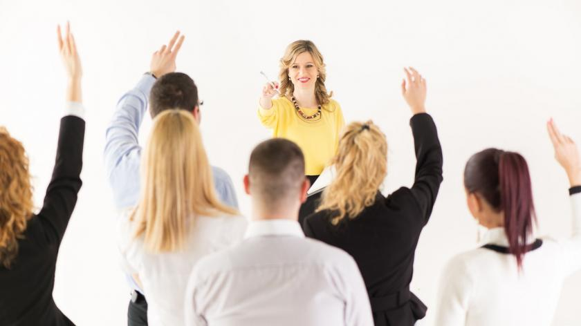 woman pointing to people raising hands