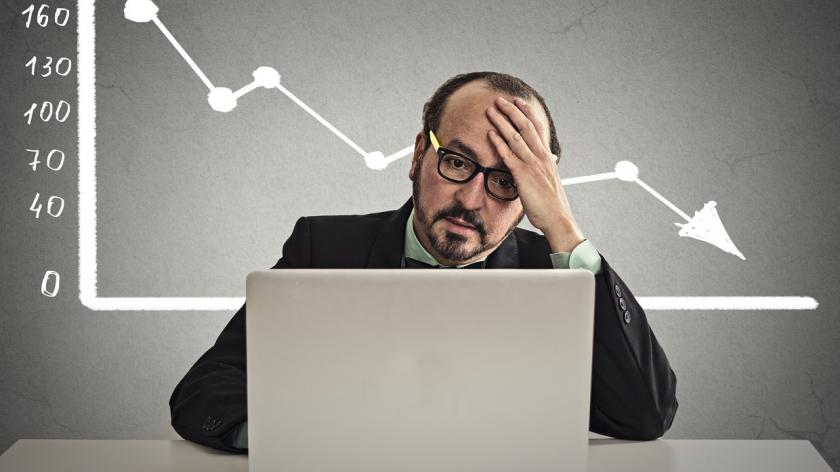 stressed man with declining value chart behind him