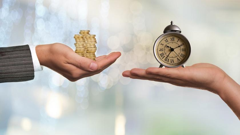 hands holding coins and a clock