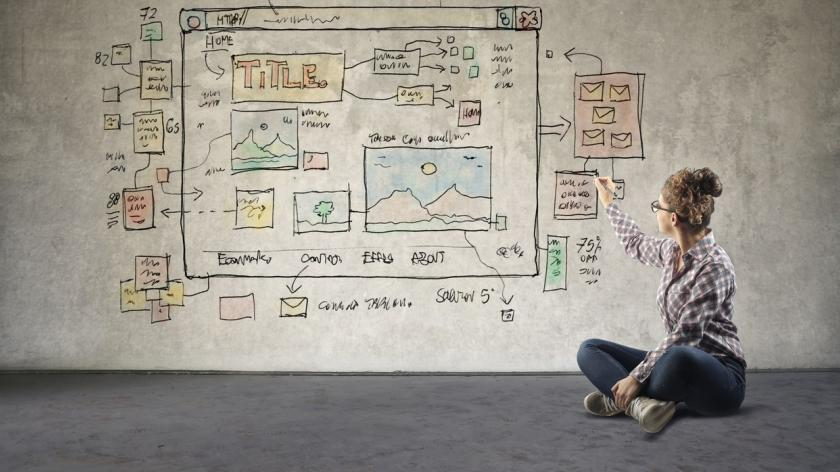 woman drawing website design on a wall